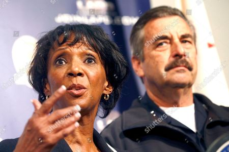 Los Angeles District Attorney Jackie Lacey, left, talks while Los Angeles Police Chief Charlie Beck looks on during a news conference in Los Angeles, . Los Angeles police say three people are in custody and a fourth is being sought in connection with a deadly fire that struck an apartment building in 1993. Two men were arrested Feb. 3 and a woman was already in custody in connection with the fire. Police will ask the district attorney to file homicide charges with special circumstances involving multiple victims, gang affiliations and arson
