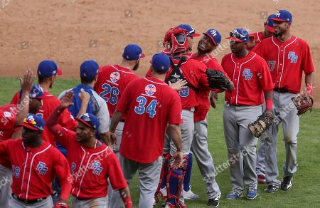 Puerto Rico's Criollos de Caguas relief pitcher Ricardo Gomez, fourth from right, is congratulated by his teammates after their semifinal victory over Venezuela's Aguilas de Zulia in the 2017 Caribbean Series baseball tournament, in Culiacan, Mexico, . Puerto Rico held off Venezuela 9-6 on Monday to reach the Caribbean Series championship game