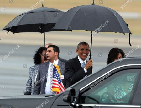 Us President Barack Obama (c) Smiles While Holding an Umbrella For Firts Lady Michelle Obama (r) Upon Their Arrival to the Jose Marti Airport in Havana Cuba 20 March 2016 Others Are not Identified Barack Obama Arrives in Cuba For an Official Visit Until 22 March to Seal the Process of Rapprochement with the Communist-ruled Island Obama is Accompanied by His Wife Michelle His Daughters Malia and Sasha and His Mother-in-law Marian Robinson the Visit of Obama to Cuba From 20 to 22 March 2016 is the First Visit of a Us President to Cuba Since Us President Calvin Coolidge's Visit 88 Years Ago Cuba Havana
