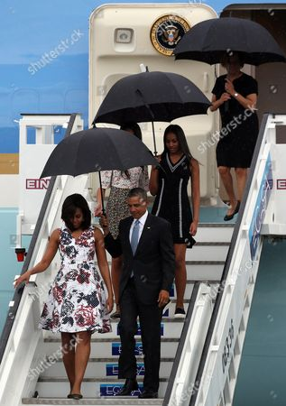 Us President Barack Obama (front R) Carries an Umbrella As He and First Lady Michelle Obama (front L) Disembark From 'Air Force One' Upon Their Arrival on Jose Marti Airport in Havana Cuba 20 March 2016 Walking Behind Are Their Daughters Malia (c-r) and Sasha Obama (c-l Hidden) Barack Obama Arrives in Cuba For an Official Visit Until 22 March to Seal the Process of Rapprochement with the Communist-ruled Island Obama is Accompanied by His Wife Michelle His Daughters Malia and Sasha and His Mother-in-law Marian Robinson the Visit of Obama to Cuba From 20 to 22 March 2016 is the First Visit of a Us President to Cuba Since Us President Calvin Coolidge's Visit 88 Years Ago Cuba Havana