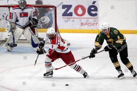 Stock Photo of North Korean Hyok an Chol (l) Vies For the Puck with Australian Austin Mckenzie (r) During Their Group B Ice Hockey World Tournament Second Division Game at the Ice Dome in Mexico City Mexico 14 April 2016 Mexico Mexico City