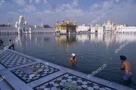 Stock Photo of Golden Temple. Men bathing in the sacred pool surrounding the temple. Amritsar Punjab INDIA