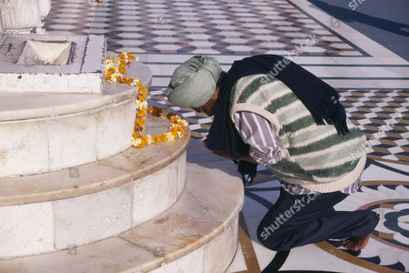 Golden Temple.  Barefoot Sikh pilgrim kneeling at shrine to pray with garland of marigold flowers laid out on marble steps. Amrtisar Punjab INDIA