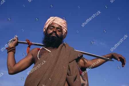 SIkh man holding Holy Kirpan Sword for the defence of the weak.  Three-quarter view looking up from below. Delhi  INDIA