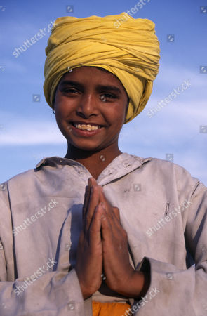 Stock Image of Portrait of smiling Sikh boy wearing yellow turban making gesture of greeting or namaste with his hands. Amritsar Punjab INDIA