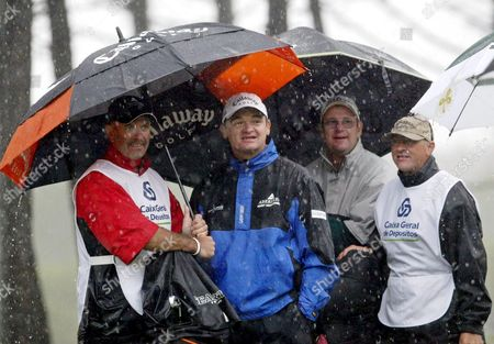 Scotish Golfer Paul Lawrie (2-l) and English Golfer Stuart Little (2-r) Shelter Under Umbrelas During a Rain Shower That Halted Play at the Third Round of the 49th Edition of the Portuguese Open Saturday 02 April 2005 at Quinta Da Marinha Near Cascais Portugal Cascais