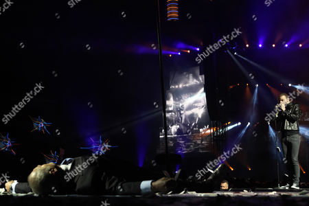 Bass Guitarist Christopher Wolstenholme of British Rock Band Muse Plays Harmonic As an Actor Lays on the Floor During Their Perform on Stage at the Dragao Stadium in Porto Portugal 10 June 2013 Portugal Porto