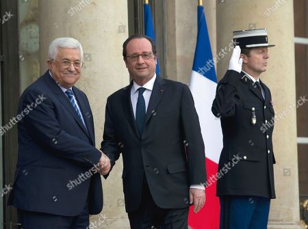 """President Francois Hollande, right, greets Palestinian leader Mahmoud Abbas prior to their meeting at the Elysee Palace in Paris, France,. Saeb Erekat, secretary general of the Palestinian Liberation Organization, has told The Associated Press that Israeli legislation to retroactively legalize thousands of West Bank settlement homes is """"putting the last nail in the coffin of the two-state solution"""