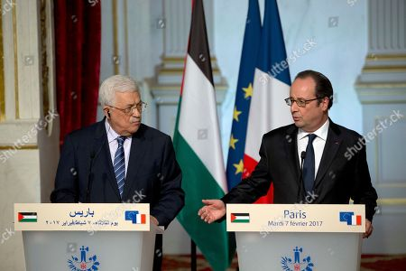 """France's President Francois Hollande, right, gestures during a joint press conference while Palestinian leader Mahmoud Abbas looks, after their meeting at the Elysee Palace in Paris, France, . Saeb Erekat, secretary general of the Palestinian Liberation Organization, has told The Associated Press that Israeli legislation to retroactively legalize thousands of West Bank settlement homes is """"putting the last nail in the coffin of the two-state solution"""
