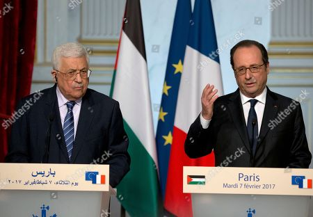 """President Francois Hollande, right, gestures during a joint press conference with Palestinian leader Mahmoud Abbas after their meeting at the Elysee Palace in Paris, France, . Saeb Erekat, secretary general of the Palestinian Liberation Organization, has told The Associated Press that Israeli legislation to retroactively legalize thousands of West Bank settlement homes is """"putting the last nail in the coffin of the two-state solution"""