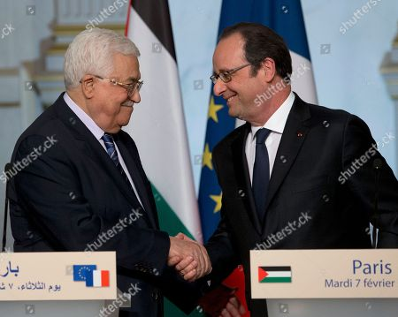 """President Francois Hollande, right, shakes hands with Palestinian leader Mahmoud Abbas after a joint press conference at the Elysee Palace in Paris, France, . Saeb Erekat, secretary general of the Palestinian Liberation Organization, has told The Associated Press that Israeli legislation to retroactively legalize thousands of West Bank settlement homes is """"putting the last nail in the coffin of the two-state solution"""