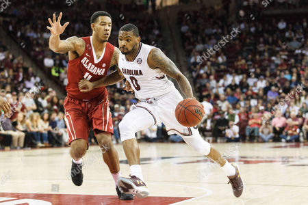 Stock Photo of Gamecocks guard Sindarius Thornwell (0) drives to the basket against Crimson Tide forward Shannon Hale (11) in the NCAA Basketball matchup at Colonial Life Arena in Columbia, SC