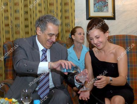 Spanish Star Tenor Placido Domingo (l) Pours Mineral Water Into the Glass of Hungarian Soprano Andrea Rost During Their Press Conference in the Hotel Meridien in Budapest on Tuesday July 26 2005 Domingo is Due to Give a Concert on 29 July and to Record an Album in Budapest Hungary Budapest
