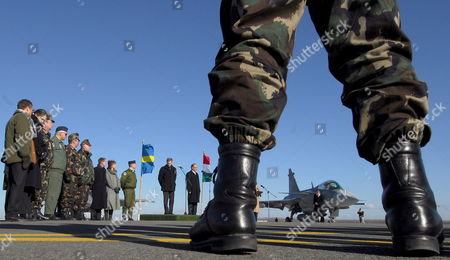 A Swedish-made Gripen Fighter Jet is Seen Far Away During the Handing Over Ceremony of the Last Batch of Three Gripen Air-fighters at the Kecskemet Air Base of the Hungarian Army in Kecskemet 83 Kms Southeast of Budapest 28 January 2008 in the Centre From Left is Sweden's Minister of Defense Sten Tolgfors Next to Him His Hungarian Counterpart Imre Szekeres Hungary Purchased Altogether 14 Gripen Fighter Jets Hungary Kecskemet