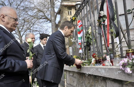 Hungary's Prime Minister Gordon Bajnai (r) - in the Company of Hungarian Foreign Minister Peter Balazs Carrying a Flower (l) - Lights Up a Candle of Condolence at Poland's Embassy in Budapest Hungary 11 April 2010 the Previous Day Poland's President Lech Kaczynski His Wife and 94 Others Died in a Plane Crash Near Smolensk Russia As They Were on Their Way to Commemorate the 70th Anniversary of the 1940 Katyn Massacre when Some 22 000 Polish Officers Uniformed Servicemen and Intellectuals Were Executed by the Soviet Nkvd in the Katyn Forest Hungary Budapest