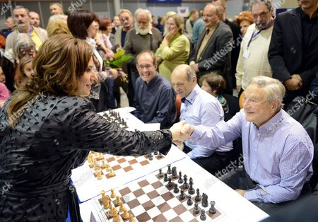 Hungarian Chess Grandmaster Judit Polgar (l) Shake Hands with Hungarian Born Us Billionaire Philanthropist and Soros Fund Management Chairman George Soros (r) Prior to the 100 Board Simultaneous Chess Game During the Vi Aquaprofit-polgar International Chess Fest in Budapest Hungary 17 November 2012 Next to Soros Hungarian Conductor Ivan Fischer Co-founder Music Director of Budapest Festival Orchestra is Seen Hungary Budapest