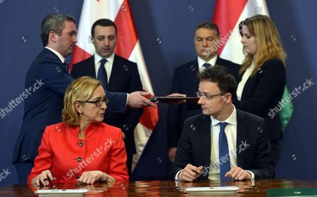 Hungarian Minister of Foreign Affairs and Trade Peter Szijjarto (r Seated) and His Georgian Counterpart Tamar Beruchashvili (l Seated) Exchange Some Words Prior to Sign an Agreement on Mutual Cooperation in the Parliament Building in Budapest Hungary 10 February 2015 Looking on in the Background Are Hungarian Prime Minister Viktor Orban (2-r) and His Georgian Counterpart Irakli Garibashvili (2-l) Others Are Unidentified Aides Epa/tibor Illyes Hungary Budapest