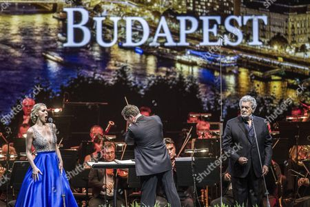 Spanish Tenor Placido Domingo (r) and Us Soprano Micaela Oeste (l) Perform on Stage with Conductor Eugene Kohn (c) During a Free Concert at the Papp Laszlo Arena in Budapest Hungary 10 August 2016 Hungary Budapest