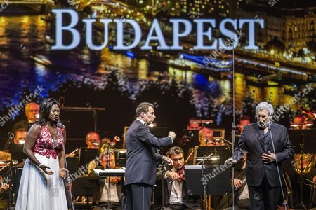 Spanish Tenor Placido Domingo (r) and Us Soprano Angel Blue (l) Perform on Stage with Conductor Eugene Kohn (c) During a Free Concert at the Papp Laszlo Arena in Budapest Hungary 10 August 2016 Hungary Budapest