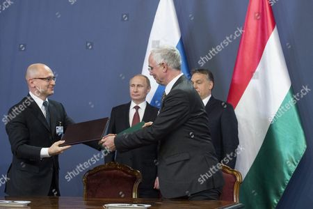 Russian President Vladimir Putin (rear Left) and Hungarian Prime Minister Viktor Orban (rear Right) Applaud As Ceo of the Rosatom State Atomic Energy Corporation of Russia Sergei Kiriyenko (l) and Hungarian Minister of Human Resources Zoltan Balog (r) Exchange Documents They've Just Signed in the Parliament Building in Budapest Hungary 17 February 2015 Putin is Staying on a One-day Working Visit in the Hungarian Capital Hungary Budapest