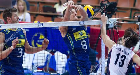 Chul-woo Park (r) of South Korea Spikes the Ball Against Eder Carbonera (l) and Murillo Endres (c) of Brazil During the Group B Match Between Brazil and South Korea For the Fivb Volleyball Men's World Championship Poland 2014 at the Spodek in Katowice Poland 06 September 2014 Poland Katowice