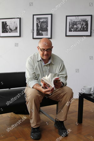 Stock Picture of South African Born Photographer Greg Marinovich Poses with His Book 'The Bang-bang Club: Snapshots From a Hidden War' As He Presents His Exhibition 'Warsaw Circus' in Cracow Poland 04 October 2012 Marinovich is a Rsa's Legend of Photojournalism War Photography and Member of the Bang-bang Club He was Awarded the Pulitzer Prize For Spot News Photography in 1991 a Leica Award and a Visa D'or the Exhibition Opens on 04 October Poland Cracow