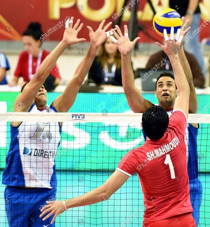 Shahram Mahmoudi (c) of Iran Spikes the Ball Against Puerto Rican Players Mannix Roman (l) and Jose Rivera (r) During the Group D Match Between Iran and Puerto Rico of the Fivb Volleyball Men's World Championship 2014 at the Arena Krakow in Cracow Poland 07 September 2014 Poland Cracow