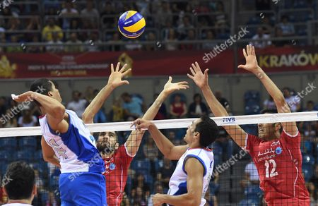 Mannix Roman (l) and Jose Rivera (2-r) of Puerto Rico in Action Against Mohammad Seyed (2-l) and Mojtaba Mirzajnpour (r) of Iran Spikes the Ball Against During the Group D Match Between Iran and Puerto Rico at the Fivb Volleyball Men's World Championship Poland 2014 at the Arena Krakow in Cracow Poland 07 September 2014 Poland Cracow