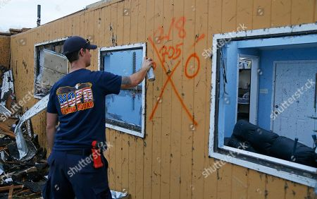 Stock Image of New Orleans Firefighter Jared Carter spray paints a search signal after conducting a secondary search of homes damaged by a tornado that touched down yesterday in eastern New Orleans, La., . Officials say tornadoes that struck in southeastern Louisiana destroyed homes and businesses, flipped vehicles and left thousands without power