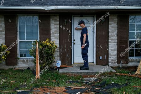 New Orleans Firefighter Jared Carter knocks on a door where a dog can be heard barking while conducting a secondary search of homes damaged by a tornado that touched down yesterday in eastern New Orleans, La., . Officials say tornadoes that struck in southeastern Louisiana destroyed homes and businesses, flipped vehicles and left thousands without power
