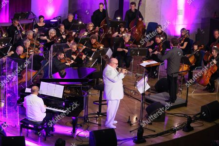 Polish Composer and Jazz Pianist Wlodek Pawlik (l) Performs on Stage with Us Trumpeter Randy Brecker (c) and the Cracow Philharmonic Orchestra Under the Baton of Polish Conductor Adam Klocek (r) During Their Concert 'Night in Calisia' in Krakow Poland 09 July 2014 Poland Krakow