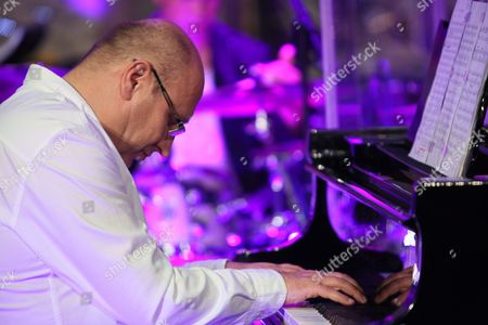 Polish Composer and Jazz Pianist Wlodek Pawlik Performs on Stage with Us Trumpeter Randy Brecker (unseen) and the Cracow Philharmonic Orchestra Under the Baton of Polish Conductor Adam Klocek (unseen) During Their Concert 'Night in Calisia' in Krakow Poland 09 July 2014 Poland Krakow