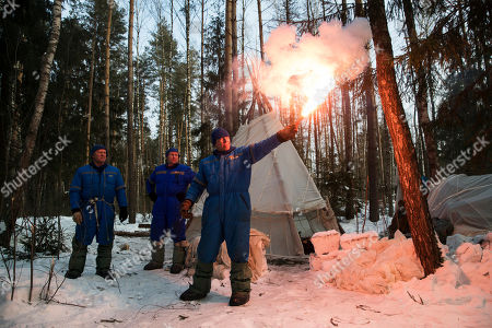 Andrew J. Feustel, Oleg Artemyev, Sergej Prokopyev NASA astronaut Andrew J. Feustel holds a flare as Russian Cosmonauts Oleg Artemyev, left, and Sergej Prokopyev stand near the hut which they built during a three-day winter training in a forest at Russian Space Training Center in Star City, outside Moscow, Russia, . The three are being trained for a future mission to the International Space Station