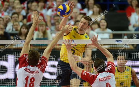 Brazil's Eder Carbonera (c) Spikes the Ball Against Poland's Marcin Mozdzonek (l) and Zbigniew Bartman (r) During Their Fivb Men's Volleyball World League Match Poland Vs Brazil in Warsaw Poland 07 June 2013 Poland Warsaw