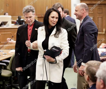 Randy Travis, Mary Travis, Blaise Baxter Country singer Randy Travis, left, walks with his wife, Mary, center, as they leave a meeting of the Senate Health and Welfare Committee, in Nashville, Tenn. Randy Travis, who suffered a stroke in 2013, attended the hearing for Stroke Awareness Day at the legislature. Dozens of country stars, from Garth Brooks to Kenny Rogers, are scheduled to perform at a tribute show Wednesday night in Nashville to honor Travis. At right is Dr. Blaise Baxter, right, of Erlanger Hospital in Chattanooga, Tenn