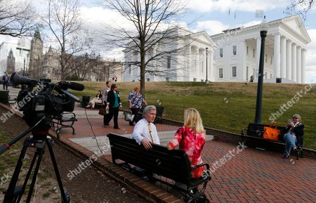 A reporter interviews former Gov. Bob McDonnell, center left, on a bench on the grounds of the Capitol in Richmond, Va., . McDonnell is due to appear at a Virginia Capitol Correspondents event Wednesday evening