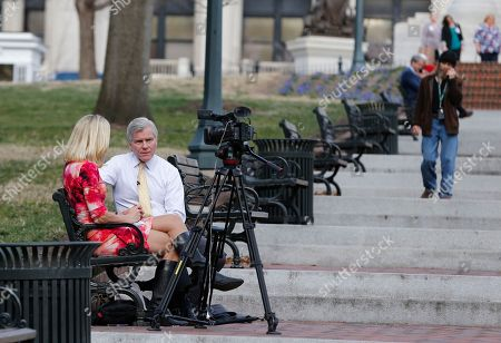 A reporter interviews former Gov. Bob McDonnell, second from left, on a bench on the grounds of the Capitol in Richmond, Va., . McDonnell is due to appear at a Virginia Capitol Correspondents event Wednesday evening