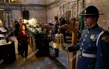 Washington State Patrol Trooper Jeffrey Eifert, right, rings a bell, at a memorial service held during a joint session of the Washington Legislature in the Senate chambers at the Capitol in Olympia, Wash. The annual candle-light service is held to remember state Senators and Representatives who have died