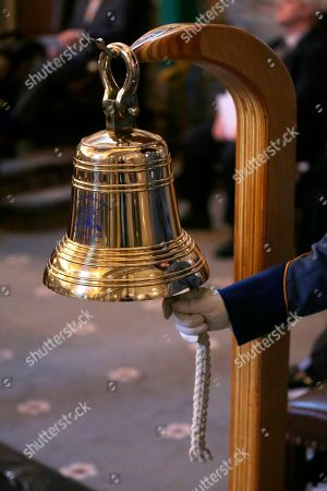 Stock Image of Washington State Patrol Trooper Jeffrey Eifert, right, rings a bell, at a memorial service held during a joint session of the Washington Legislature in the Senate chambers at the Capitol in Olympia, Wash. The annual candle-light service is held to remember state Senators and Representatives who have died