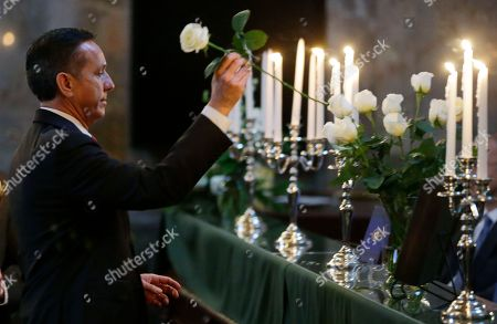 State Senator Dino Rossi, R-Sammamish, places a flower in a vase in memory of Senator Andy Hill, R-Redmond, at a memorial service held during a joint session of the Washington Legislature in the Senate chambers at the Capitol in Olympia, Wash. Rossi was appointed to replace Hill after Hill died in late 2016 of lung cancer. The annual candle-light service is held to remember state senators and representatives who have died