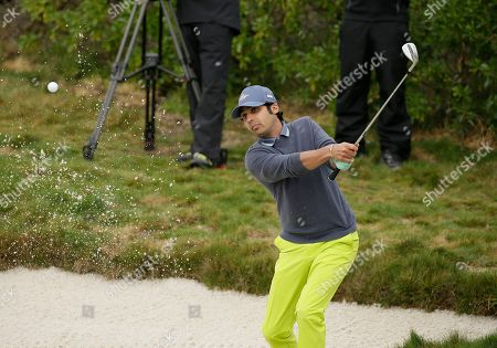 Stock Photo of Kunal Nayar hits out of a bunker onto the first green during the celebrity challenge event of the AT&T Pebble Beach National Pro-Am golf tournament, in Pebble Beach, Calif