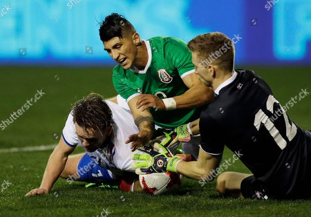 Iceland goalkeeper Frederik Schram, right, blocks the ball as Mexico's Alan Pulido, center, and Iceland's David Thor Vidarsson fall onto him during the second half of a friendly soccer match, in Las Vegas