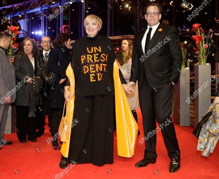 Claudia Roth, deputy president of the German parliament, wears a suit with a writing 'unpresidented' as she arrives with politician Konstantin von Notz, right, on the red carpet for the opening film 'Django' at the 2017 Berlinale Film Festival in Berlin, Germany