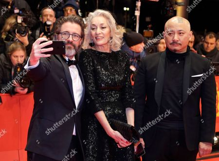 Jury member Olafur Eliasson, left, takes a selfie with Dora Bouchoucha Fourati and Wang Quan'an on the red carpet for the opening film 'Django' at the 2017 Berlinale Film Festival in Berlin, Germany