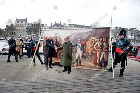 Stock Picture of Direct Descendants of the Russian Imperial Dynasty Romanovs and French Emperor Napoleon Bonaparte Prince Dimitri Romanov (c-r) and Count Alexandre Colonna-walewski (c-l) Shake Hands Standing in Front of a Print 'Farewell of Napoleon and Alexandre After the Peace of Tilsit' by an Anonymous Painter As They Are Guests of Honour at the Official Opening of the Exhibition 'Alexander Napoleon and Josephine a Story of Friendship War and Art From the Hermitage' at the Hermitage Amsterdam in Amsterdam Netherlands 27 March 2015 the Exhibition Will Run From 28 March to 08 November Netherlands Amsterdam