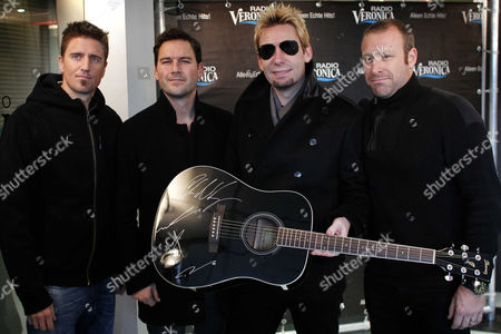 (l-r) Daniel Adair Ryan Peake Chad Kroeger and Mike Kroeger of Canadian Rock Band Nickelback Pose with a Signed Guitar in Naarden the Netherlands 18 November 2013 the Proceeds From the Auction of the Instrument Will Be Donated to the Victims of Typhoon Haiyan in the Philippines the Dutch Public and Commercial Radio and Tv Stations Are Raising Money For the Victims of the Typhoon Giro 555 an Account of the Cooperating Aid Organizations Has Been Opened on 11 November and Has Raised More Than 10 000 000 Euro So Far Reports State Netherlands Naarden