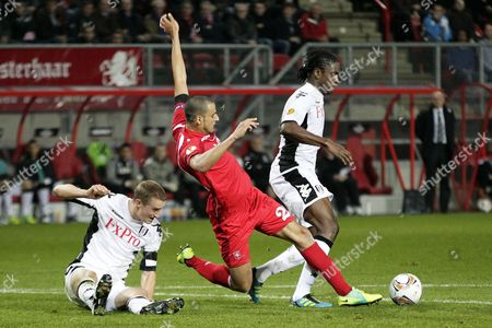 Nacer Chadli of Fc Twente (c) Fights For the Ball with Fulham Players Dickson Etuhu (r) and Brede Hangelandt (l) During the Uefa Europa League Soccer Match Fc Twente - Fulham in Enschede Netherlands 01 December 2011 Netherlands Enschede