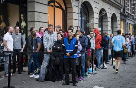 Customers Stand in a Queue in Front of the Apple Store in Amsterdam the Netherlands 16 September 2016 at the Start of Iphone 7 Sales Apple's Share Price Jumped More Than Three Per Cent Following Reports It Had Already Sold out Certain Iphone 7 Models with Specific Colours Especially in 'Jet Black' Colour and the Plus Models Apple Also Said Online Orders May Take Longer to Due to Brisk Sales of Its Latest Flasghip Smartphone Netherlands Amsterdam