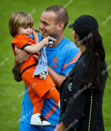 Dutch National Team Soccer Player Wesley Sneijder Carries the Son of John Heitinga Next to His His Wife Yolanthe Sneijder-cabau After the First Training Session of the Netherland's National Soccer Team in Lausanne Switzerland 18 May 2012 Netherlands National Football Team is in Lausanne For a Training Camp in Preparation For the Uefa Euro 2012 Soccer Championship Hosted Jointly by Poland and Ukraine Switzerland Schweiz Suisse Lausanne