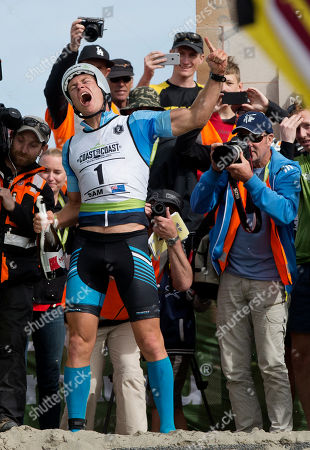 """New Zealand's Sam Clark celebrates after crossing the finish line in Christchurch to win the """"Longest Day"""" 243km race across the South Island of New Zealand, . The race from the West Coast across the southern Alps to the East Coast of New Zealand is one of the world's longest running multi-sports events with athletes running, cycling and kayaking their way to the finish line"""